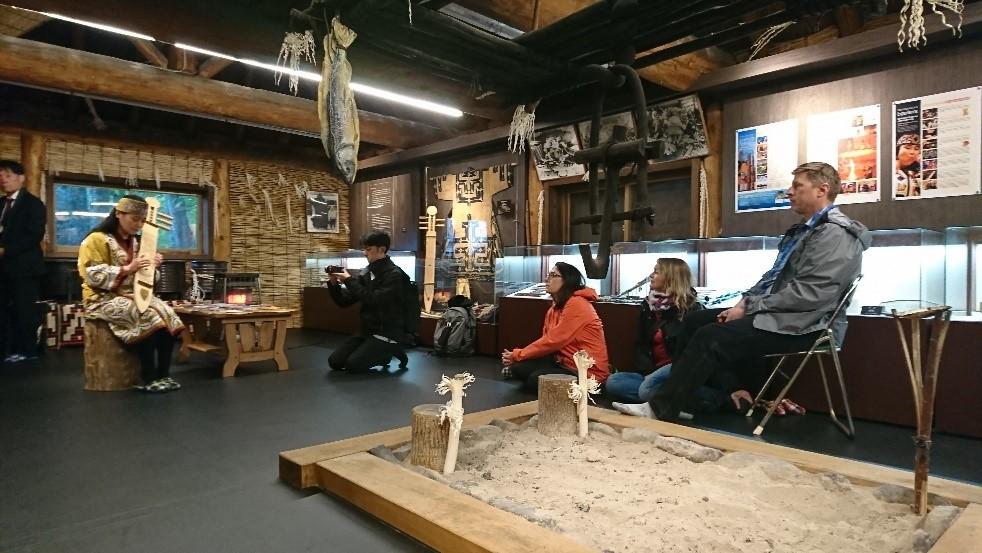 アイヌコタンのチセ(小屋)内で伝統楽器の演奏を鑑賞するATTA関係者